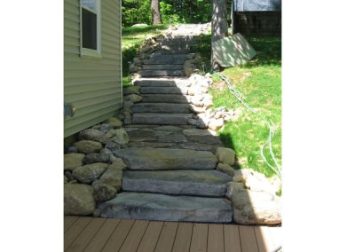 photo of granite steps in a retaining wall built by Ideal landscape of Holden MA
