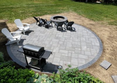 round Unilock patio in Shrewsbury Ma by Ideal Landscaping